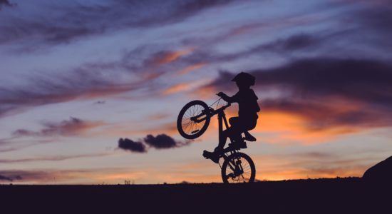 child on bike with sunset