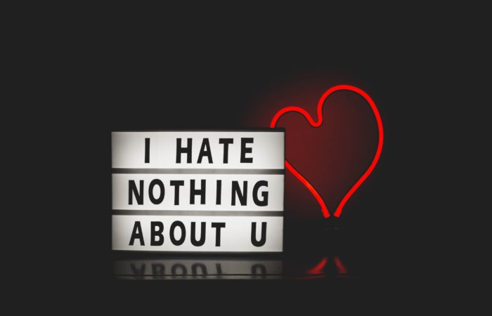 """A neon sign that says """"I HATE NOTHING ABOUT U"""" with a heart"""