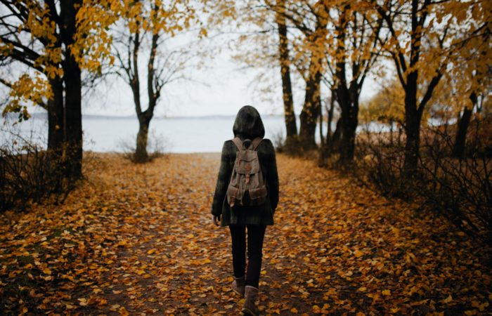 A woman walking on a pathway with falling leaves near a lake