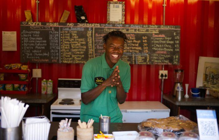 A smiling barista behind a counter