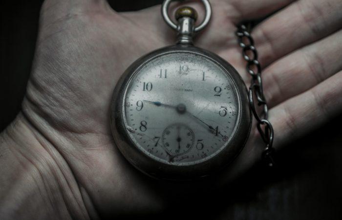 A hand holding an antique pocket watch