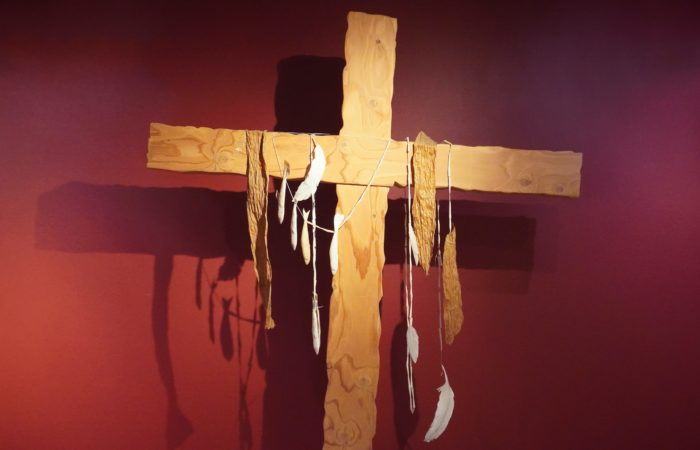 A cross decorated with feathers