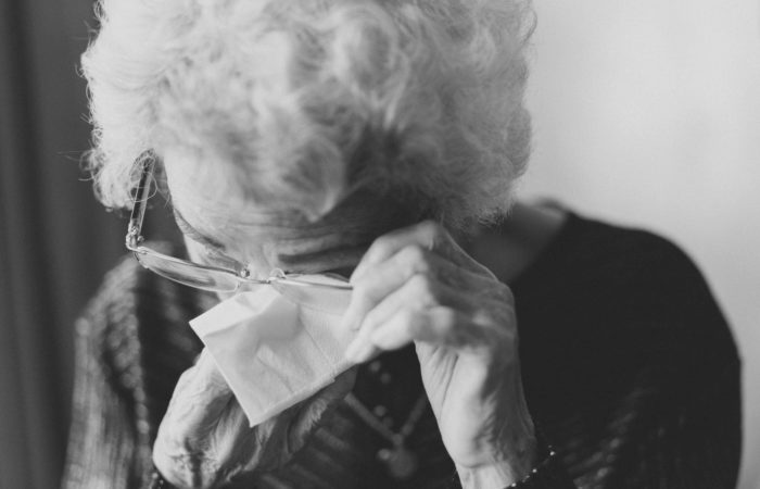 An old woman wiping tears from her eyes