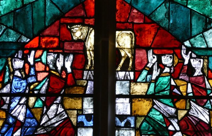 A stained glass window showing the Israelites bowing before the golden calf