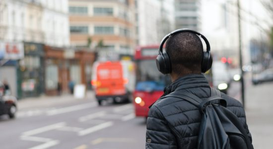 A young man with headphones on a busy street