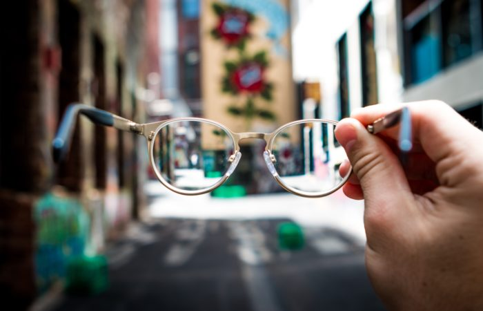 A person holding up eyeglasses to look down a city street