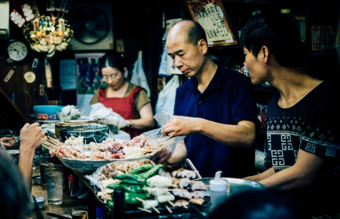A family at an Asian restaurant preparing a large meal