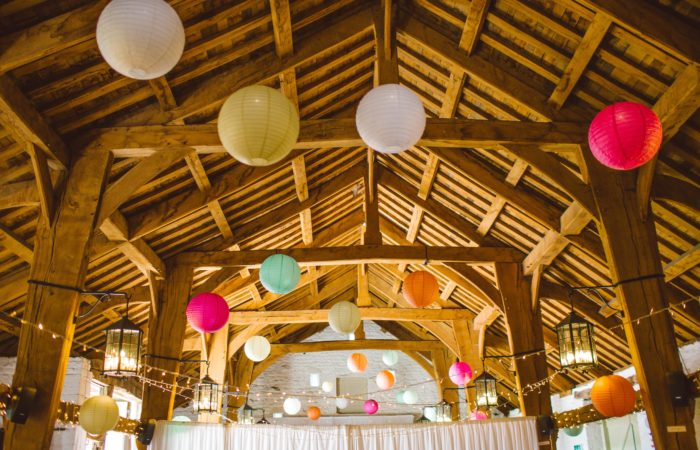 A barn set up for a party with tables and many colored lanterns