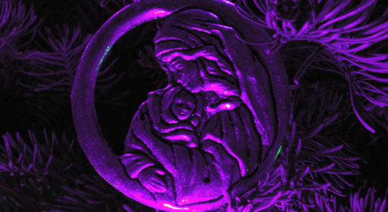 A nativity ornament of Mary and the Christ Child, seen under a purple light