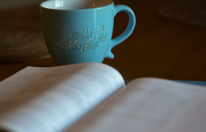 """An open Bible and a coffee cup that says """"Be still and know that I am God"""""""