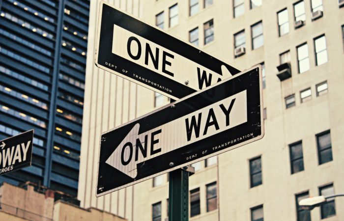 Two one way signs on a New York street corner pointing perpendicular directions.