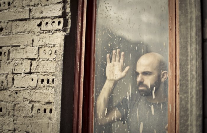 A man looking through a dirty window