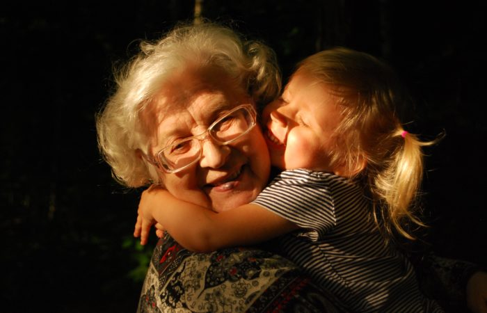 A young child hugging a grandmother