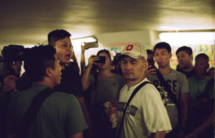 A man shouting at another man while a group of onlookers film them