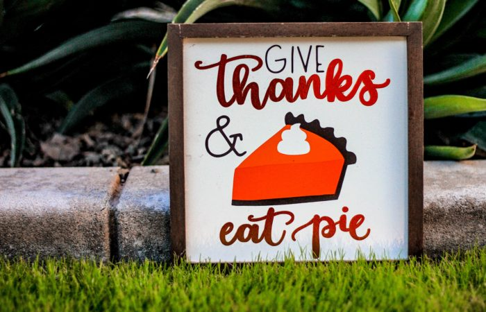 """A sign that says """"Give thanks and eat pie"""" with an image of pumpkin pie"""