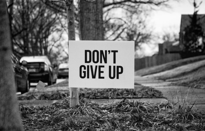 """A sign saying """"Don't Give Up"""" in someone's front yard"""