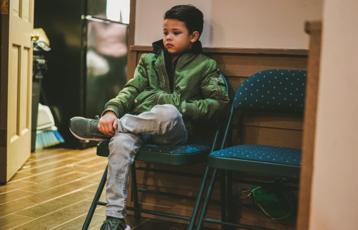 A small boy waiting on a folding chair in an office