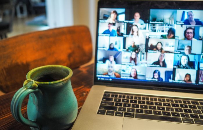 A mug next to a computer where many people are participating on a Zoom call