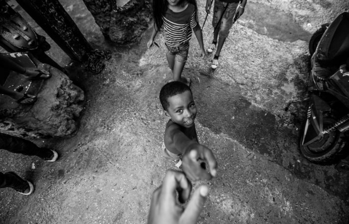 A crowd of children, one of whom is reaching out to the photographer