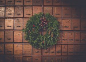 A Christmas wreath on a wall full of many wooden boxes