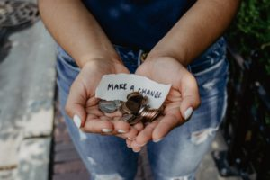 "A woman holding a pile of coins and a sign reading ""Make a Change"""