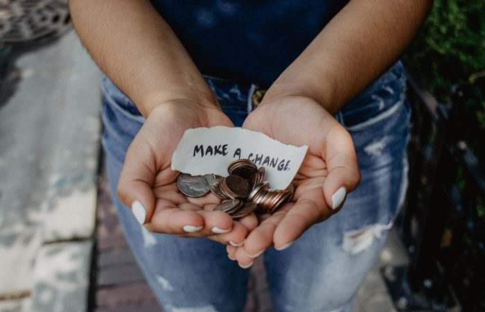 """A woman holding a pile of coins and a sign reading """"Make a Change"""""""