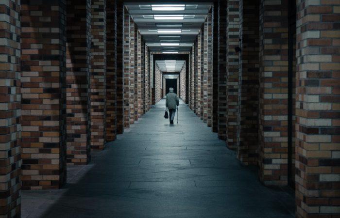An old man walking alone down a long hallway