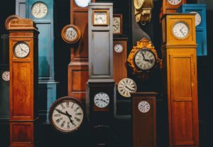 A large group of old clocks, mostly grandfather clocks