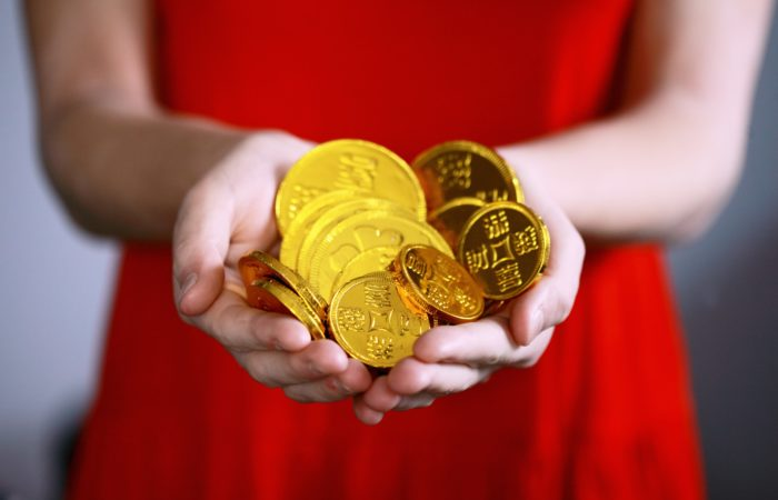 A woman dressed in red holding out a handful of chocolate coins