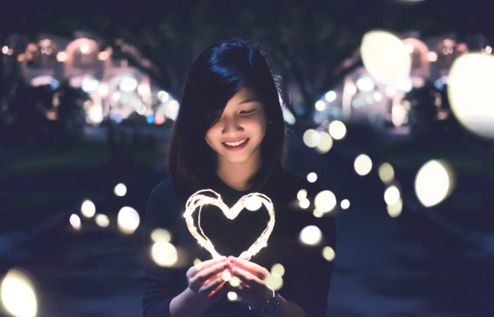 A woman holding a lit-up heart