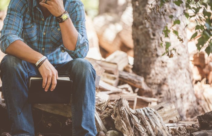 A man sitting on a log reading a Bible