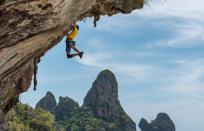 A mountain climber clinging to the side of a cliff