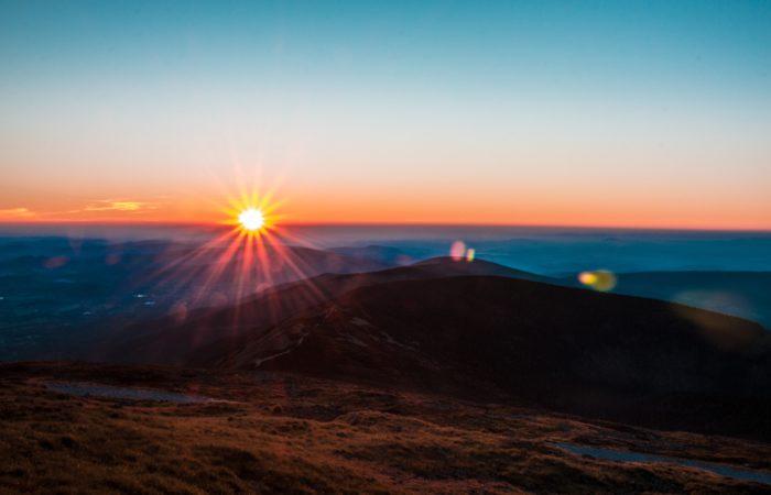 A sunrise over rolling hills