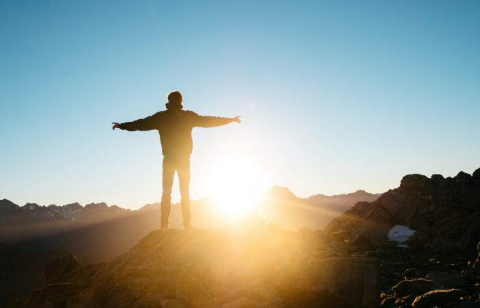 A man standing at the top of a mountain looking at a sunrise