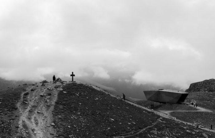 A man climbing a mountain towards a cross at the top