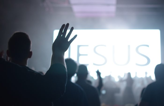 People raising their hands to worship in front of a sign that says Jesus