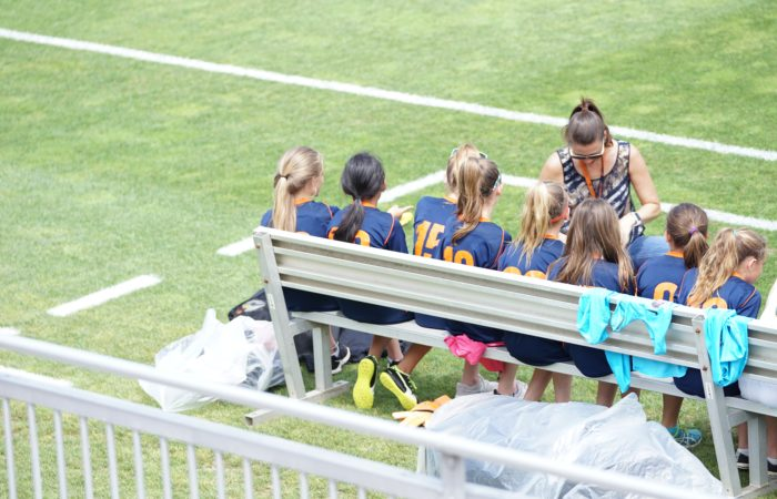 A coach with a bench full of soccer players