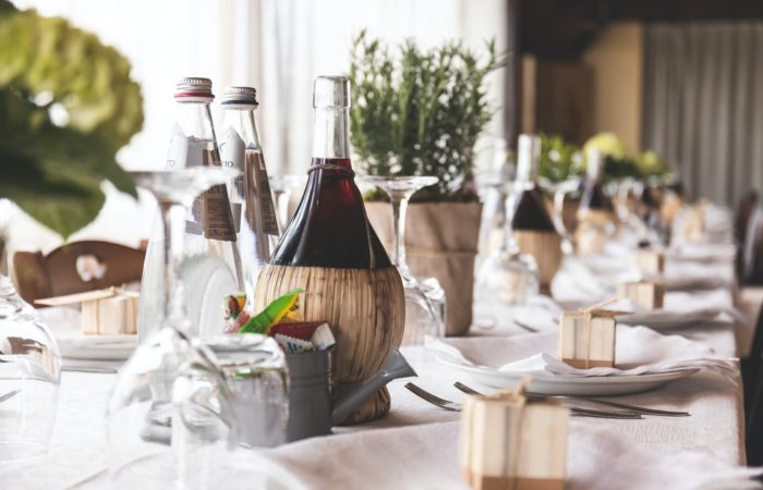 A wine carafe on a table next to water bottles at a wedding banquet