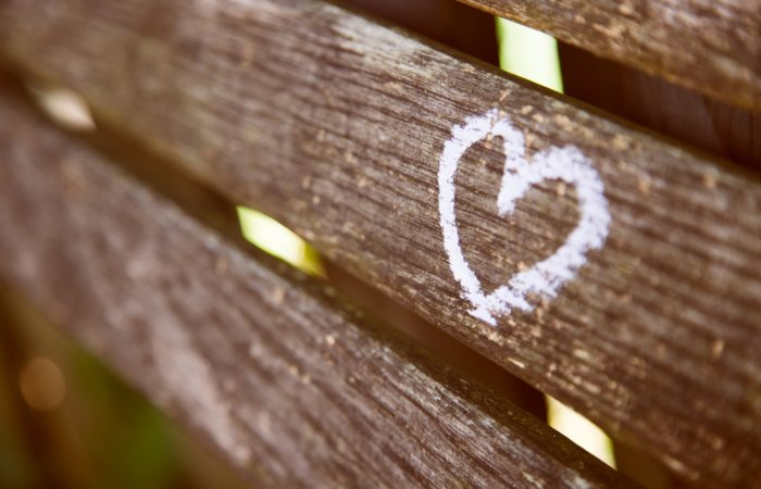 A painted white heart on a park bench