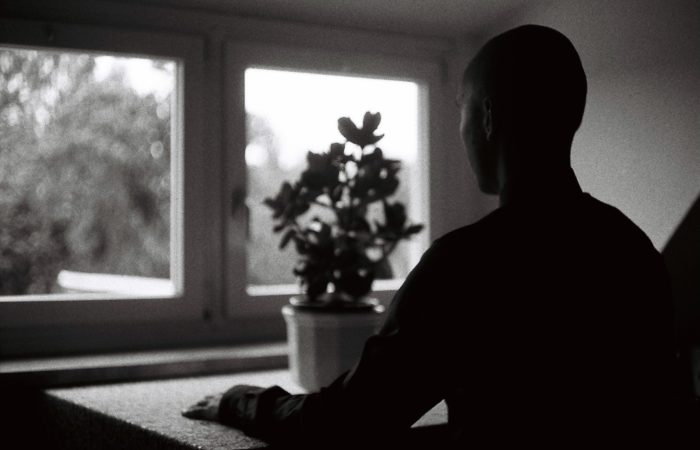 A man looking expectantly out a window