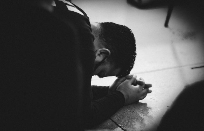 A man kneeling on the floor and praying intently