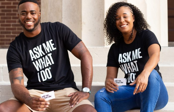 """A man and a woman sitting on the front steps of a building wearing T-shirts and holding business cards that say """"Ask Me What I Do"""""""