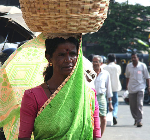 Sari-clad woman in Mysore, India, balancing a basket of chikoo on her head.