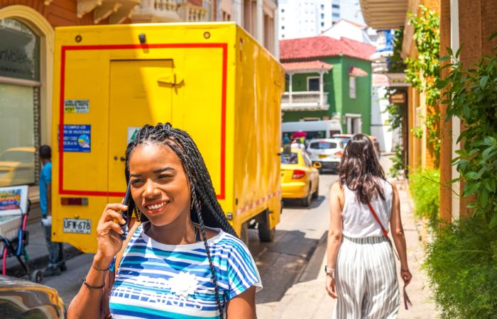 A young woman talking on a cell phone on a colorful, crowded street