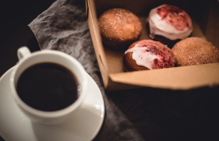 A cup of black coffee and a box of muffins