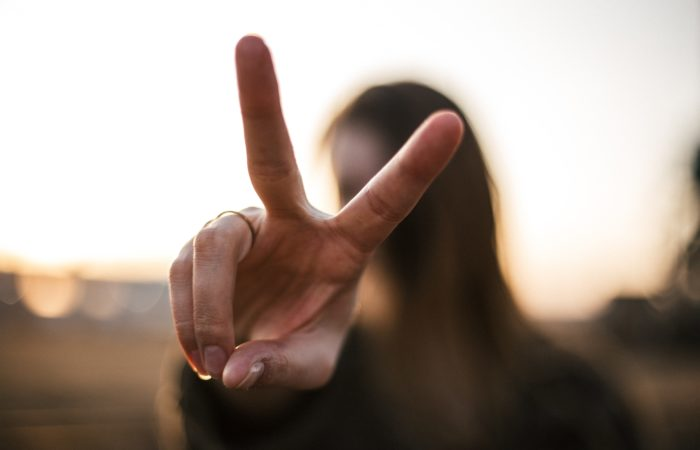 A woman making a peace sign with her face hidden