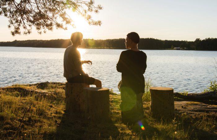 Two men talking beside a lake at sunset