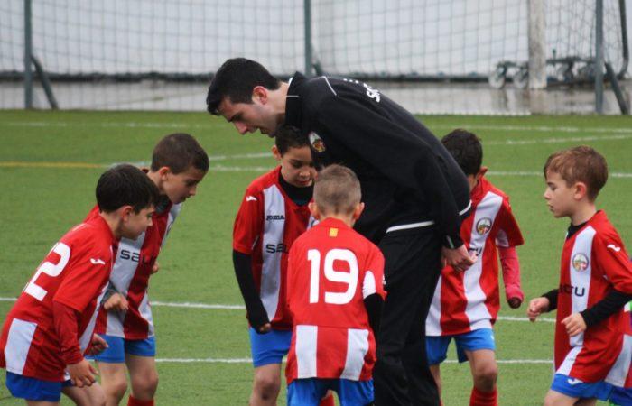 man coaching children soccer team