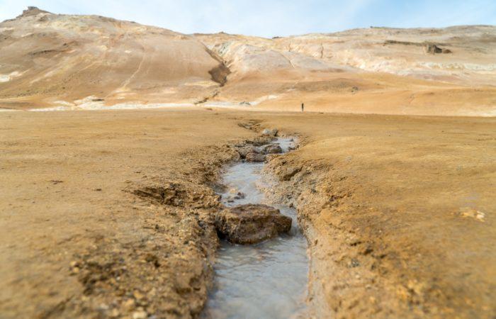 A stream running through a desert towards the mountains