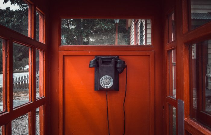 An old-fashioned rotary dial phone in a phone booth